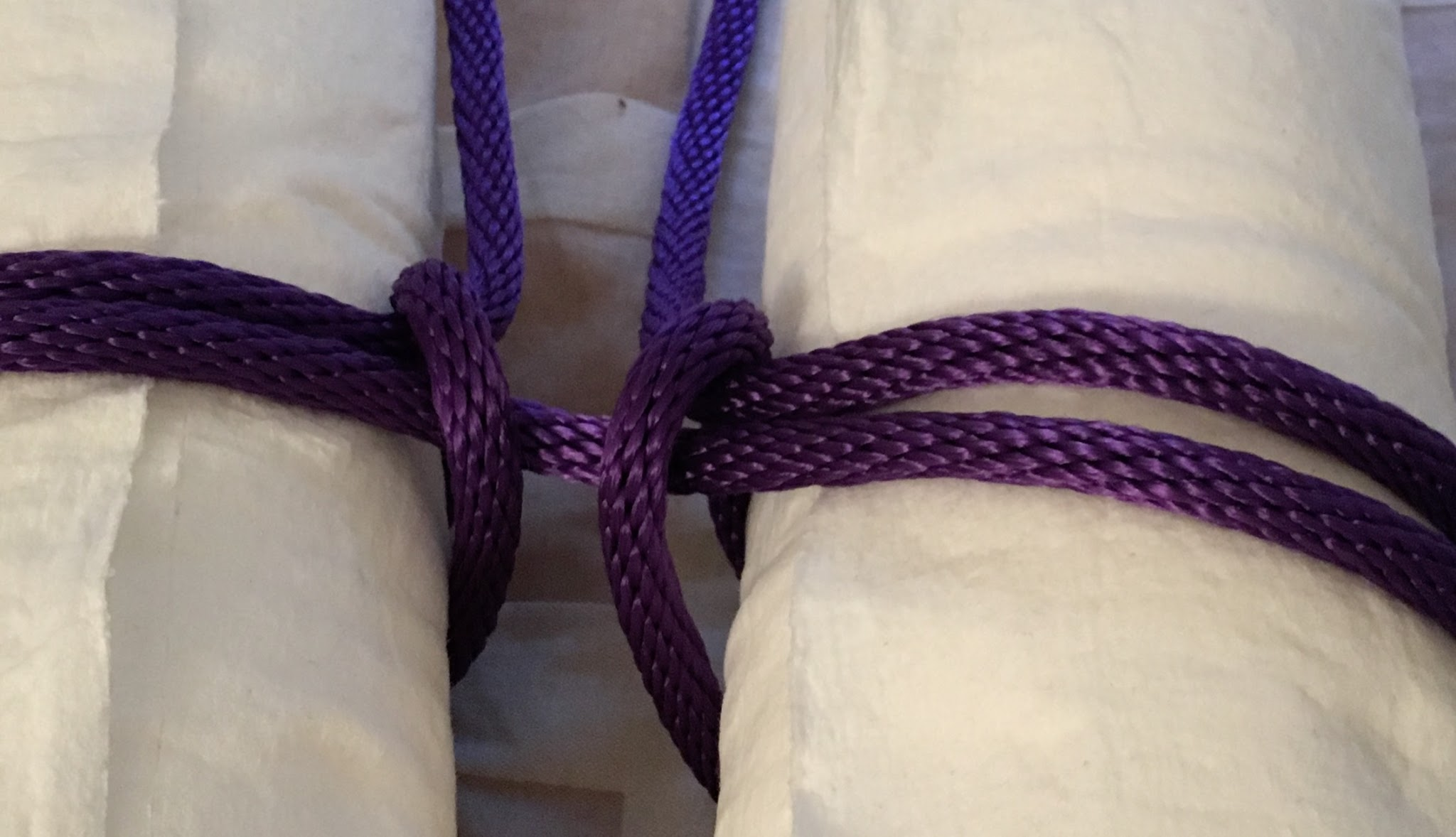 Close-up of rope tied around two paper towel rolls
