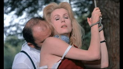 Scene from the movie Belle de Jour in which Catherine Deneuve's wrists are bound with rope while a man kisses her neck.