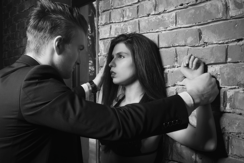 Man pinning a woman's wrists against a brick wall.