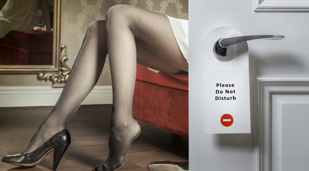 """Image of woman sitting on a chair wearing panty hose behind a door with a """"Please do not disturb"""" sign on it"""