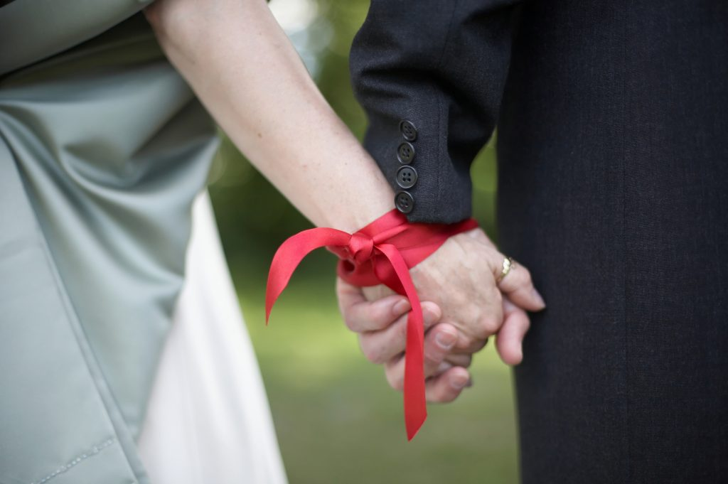 Man and woman holding hands, their wrists tied together with a ribbon