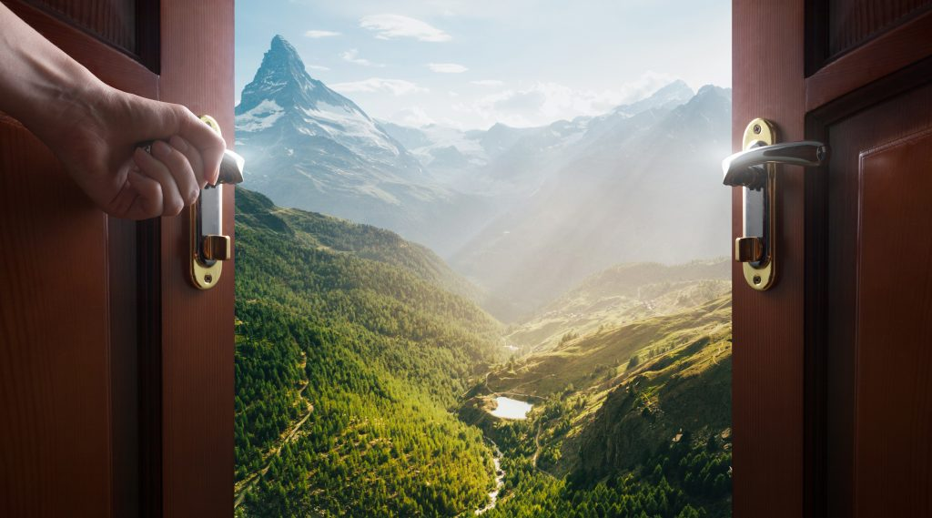 Doors opening to a dramatic view of a lush valley with mountains in the background.