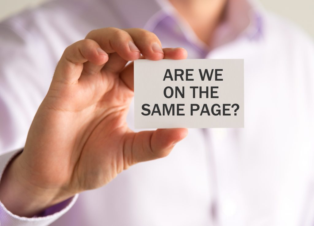 """Man holding a card that says """"Are we on the same page?"""""""