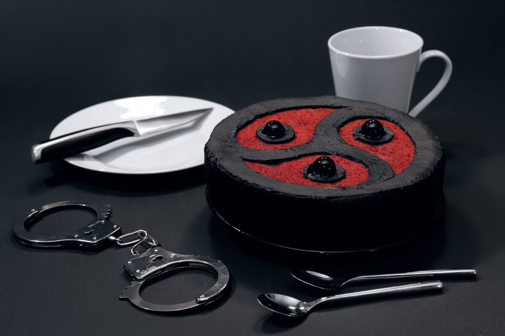 Cake in the shape of a triskelion, surrounded by a mug, two spoons, handcuffs, a plate and a knife.