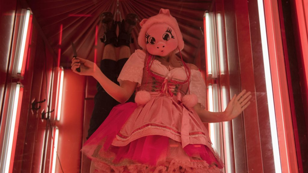 Scene from season 2 of Killing Eve; woman in flouncy dress wearing a pig mask and holding a knife